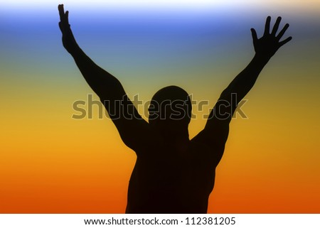 Silhouette of a man with outstretched arms on a rainbow background - stock photo