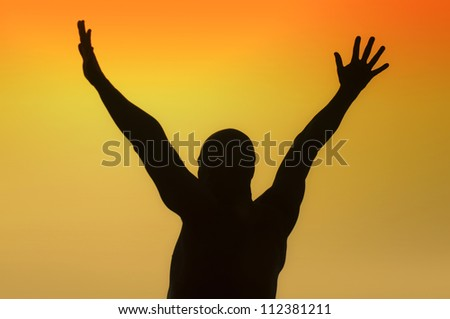 Silhouette of a man with outstretched arms on a yellow background - stock photo