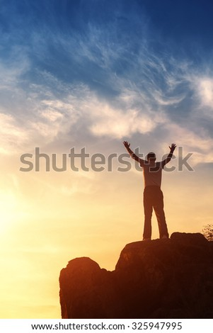Silhouette of a man with raised-up arms at the beautiful sunset on the mountain. Background - stock photo