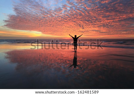 Silhouette of a man with sunset reflection at Sabah, Borneo, Malaysia - stock photo