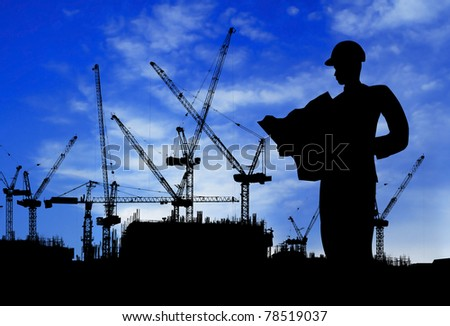 silhouette of a man working on construction site during day time - stock photo