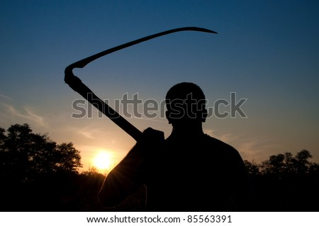 Silhouette of a maniac with a scythe in the hands at sunset - stock photo