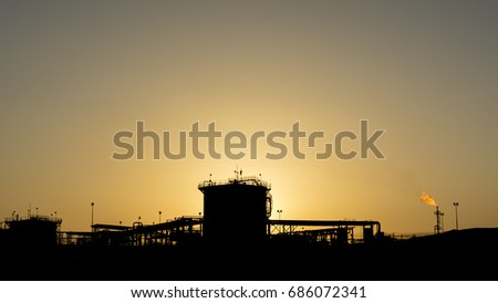 Silhouette of a manifold refinery plant in the oilfield at sunset
