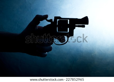 Silhouette of a mans hand with a handgun in blue - stock photo