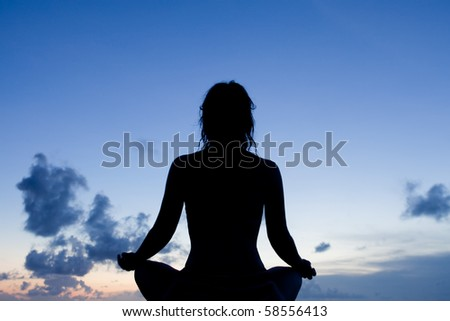 Silhouette of a meditating woman during twilight - stock photo