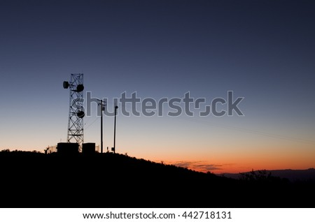 silhouette of a microwave antenna tower against an evening sky - stock photo