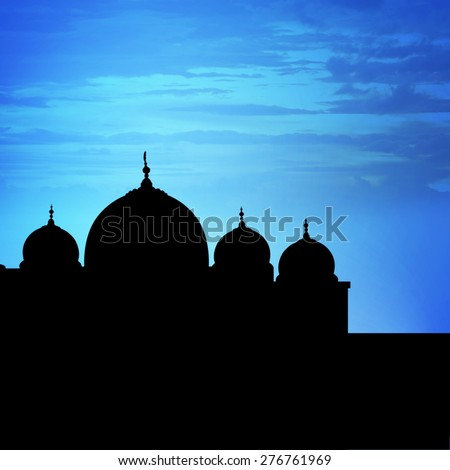 Silhouette of a mosque in sunset with blue sky background - stock photo