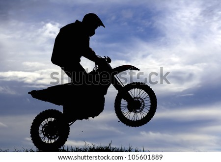 Silhouette of a motocross racer under blue cloudy sky