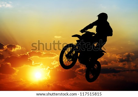 Silhouette of a motorcyclist on a background of dark sky - stock photo