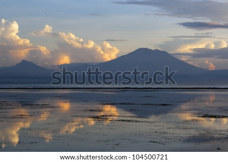 Silhouette of a mountain and its reflection on water in Bali - stock photo