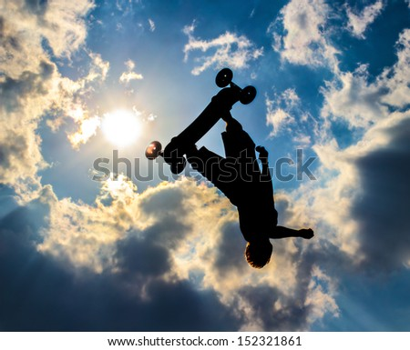 Silhouette of a mountainboard  flying in background the sun and blue sky with clouds