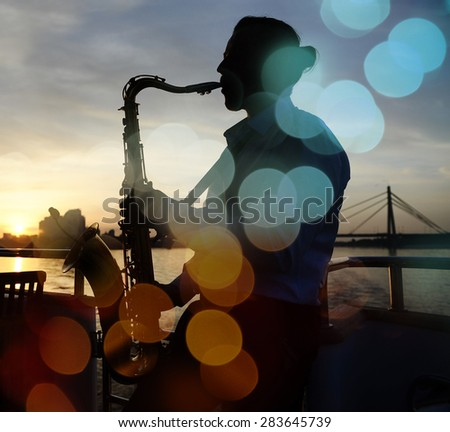 silhouette of a musician with a saxophone near the river with night lights