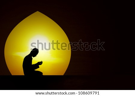 Silhouette of a muslim praying at sunset during the month of ramadan - stock photo