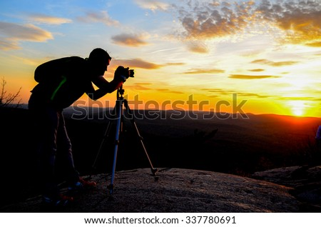 Silhouette of a nature photographer framing a shot, taking pictures at sunset in the mountains