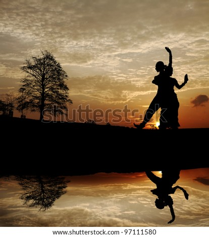 Silhouette of a pair of Indian classical dancers posing by a lakeside with their reflection in the water against a dramatic fiery sunset. - stock photo