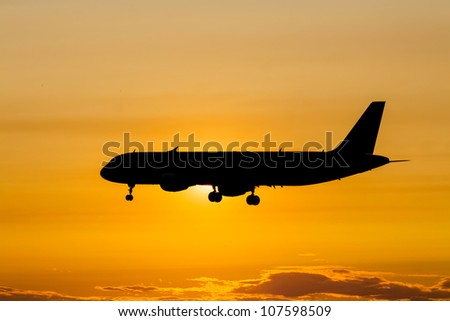 Silhouette of a passenger plane landing in sunset