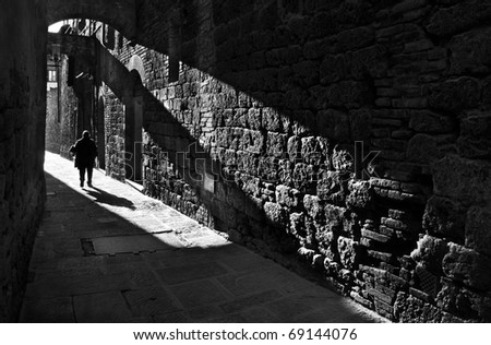 Silhouette of a pedestrian in a small street of San Gimignano , Italy, black and white photography - stock photo