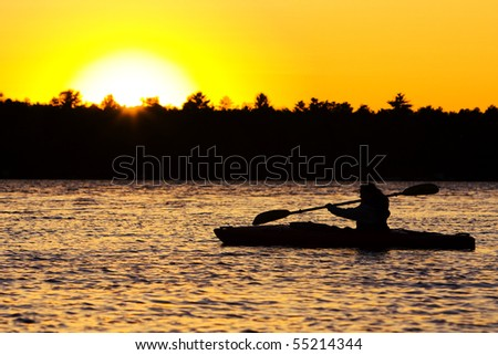 Silhouette of a person kayaking on lake at sunset.  Paddle is in mid-stroke. - stock photo