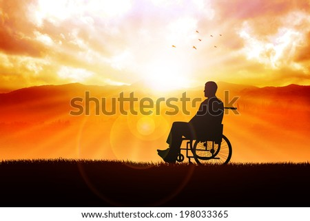 Silhouette of a person on wheelchair in the outdoor with sunrise and mountain view as the background - stock photo