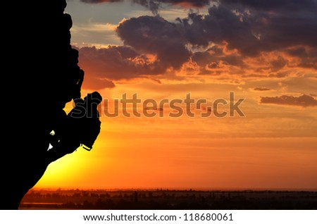 silhouette of a person without insurance climbs the rock in the background of the sunset