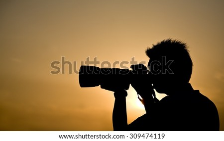 Silhouette of a photographer holding a telephoto lens - stock photo