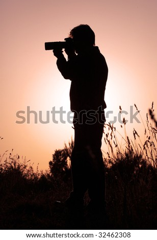 Silhouette of a photographer in the nature - stock photo