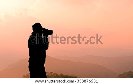 silhouette of a photographer is taking photos of misty mountain hills landscape