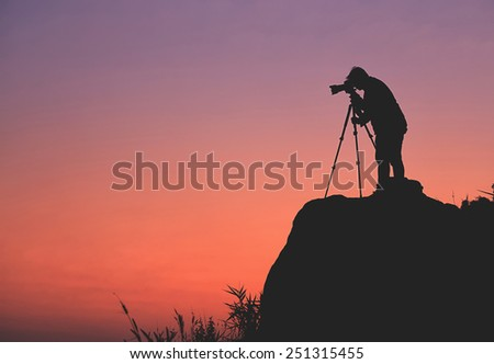 Silhouette of a photographer who shooting a sunset on the mountains - stock photo