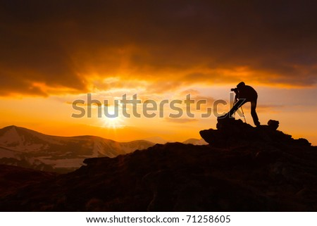 silhouette of a photographer who shoots a sunset in the mountains - stock photo