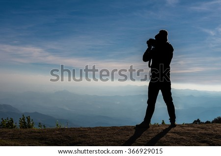 silhouette of a photographer who shoots the mountains landscape
