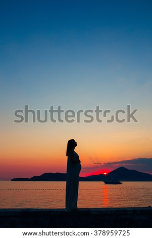 Silhouette of a pregnant woman at sunset by the sea
