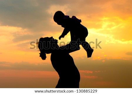 Silhouette of a pregnant woman with her daughter at sunset - stock photo