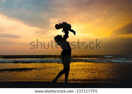 Silhouette of a pregnant woman with her daughter at sunset