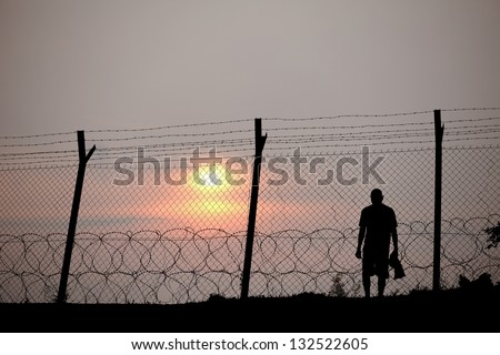 Silhouette of a prisoner behind a barbed wire fence in a concentration camp against fiery setting sun. - stock photo