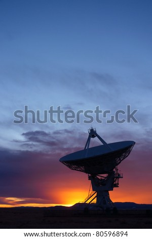 Silhouette of a radio telescope at the Very Large Array (VLA) in New Mexico, USA, at sunset - stock photo
