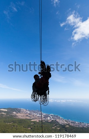 Silhouette of a rappelling man