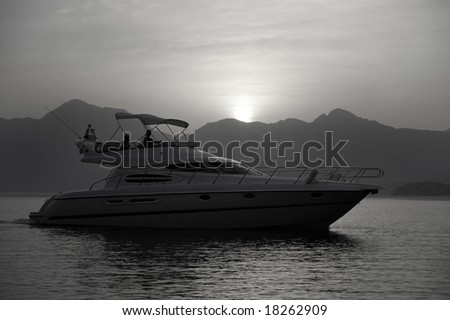 Silhouette Of A Recreational Yacht Gently Cruising In A Lake - stock photo