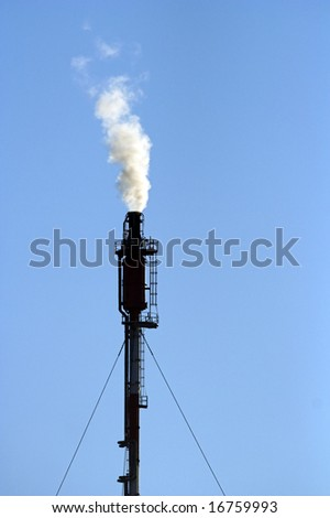 Silhouette of a refinery chimney with smoke against blue sky