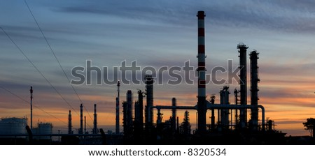 Silhouette of a refinery plant over a beautiful sunset sky.Panoramic picture,not a crop. - stock photo