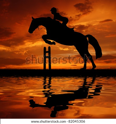 silhouette of a rider on a jumping horse - stock photo