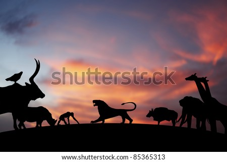 Silhouette of a roaring Lion on the horizon presiding over a kingdom of animals, against a dreamy candy colored surreal sunset. - stock photo
