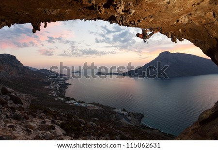 Silhouette of a rock climber against picturesque view of Telendos Island at sunset. Kalymnos Island, Greece. - stock photo