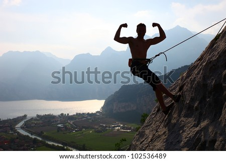 Silhouette of a rock climber flexing biceps against picturesque view of Lake Garda, Arco, northern Italy - stock photo
