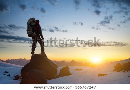 Silhouette of a rock climber on the peak. Sport and active life concept - stock photo