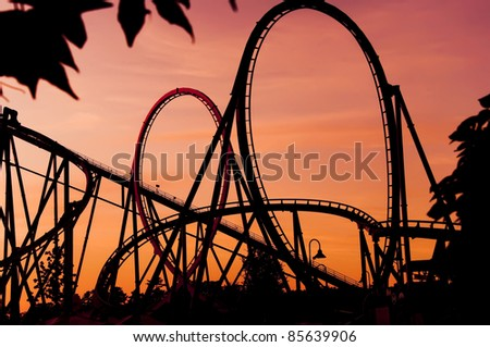 silhouette of a roller coaster at a purple sunset during a fun fair, after a sunny day - stock photo