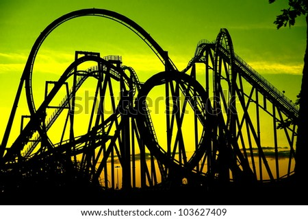 silhouette of a roller coaster at  sunset, after a sunny day - stock photo