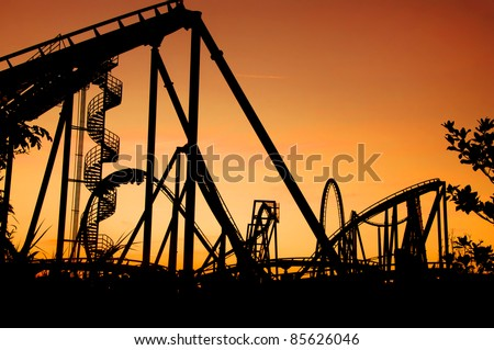 silhouette of a roller coaster during sunset at a fun fair - stock photo