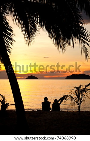 Silhouette of a romantic couple sitting on a beach under palm trees at sunset. Sunlight is shimmering off of the water. Other islands can be seen at the distance. - stock photo