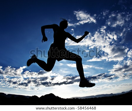 Silhouette of a runner with a beautiful sky in the background - stock photo