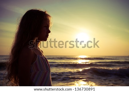 Silhouette of a sad child on the beach - stock photo